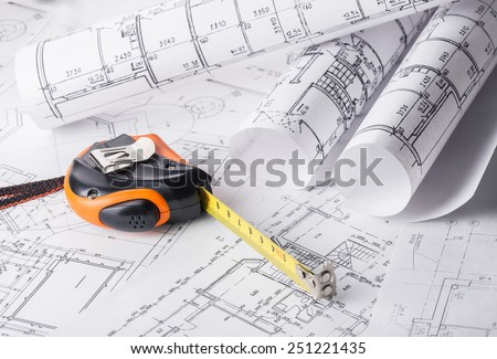 Tape measure over a construction plan drawing - stock photo