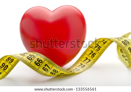 Tape measure over red heart - stock photo