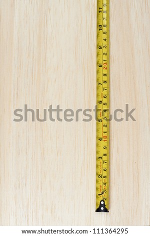Tape measure over wooden background - stock photo
