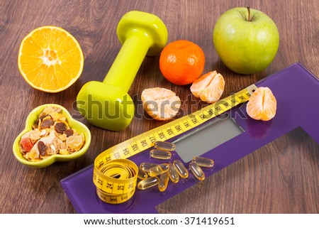 Tape measure, tablets supplements on digital bathroom scale for weight of human body, dumbbells for fitness and fresh fruits with muesli, concept of healthy lifestyle and slimming - stock photo