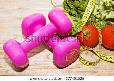 tape measure with tomatoes, vegetables and dumbbells - stock photo