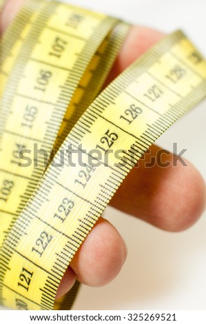 Tape measure wrapped around hands. - stock photo