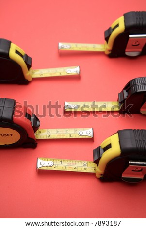 Tape measures on red background