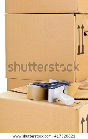 Tape roller on stack of moving carton boxes over white background