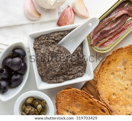 Tapenade, traditional Provence sauce with black olives, capers, garlic and anchovies. - stock photo