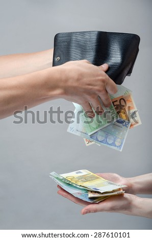 tapping out money from a purse to pay - stock photo