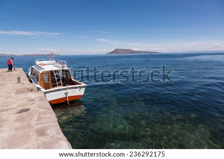 TAQUILE ISLAND, PUNO, PERU: Boat in the harbor in the Titicaca lake. - stock photo