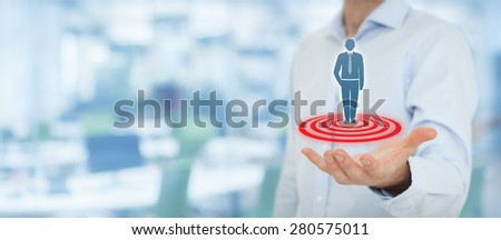 Target customer (marketing) concept. Businessman hold target customer represented by virtual icon of man standing on target. Wide banner composition, office in background.