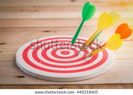target dart with target arrows over wooden background ,metaphor to target marketing or target arrow concept . - stock photo