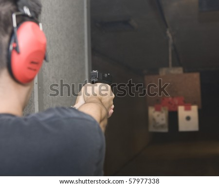Target practicing with gun In the shooting range - stock photo