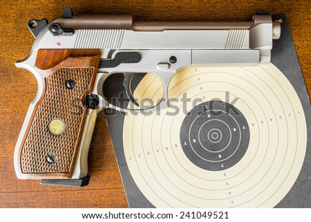 Target shooting, the gun and the target on the table. Top view - stock photo