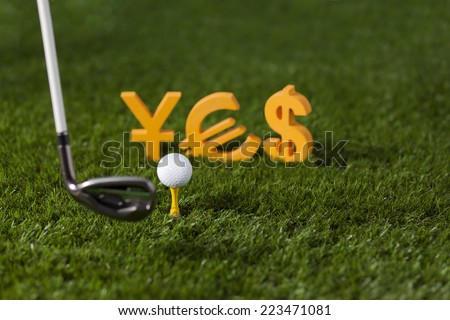 Targeting money with golf club and ball on green grass - stock photo
