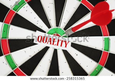 Targeting Quality Concept and a dart in center of target - stock photo
