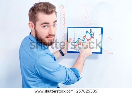 Targeting the consumers. Rear view with selective focus of young handsome man in smart casual wear pointing at marketing chart on the board while having a brainstorming  - stock photo