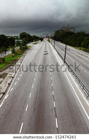Tarmac highway into a city with dark storm cloud in the horizon.  - stock photo