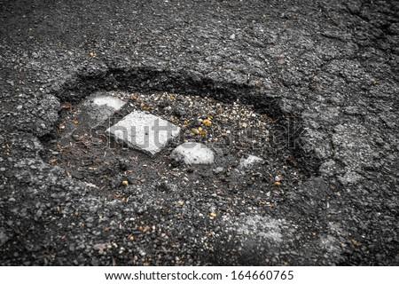 Tarmac road with big holes in Belgium - stock photo