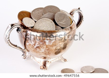 Tarnished silver plate pot filled with coins from various nations with scattered coins and white background - stock photo