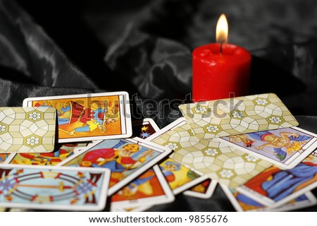 Tarot cards and burning candle - stock photo