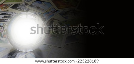 Tarot reader's website banner  -  Crystal ball with empty center laid on random scattered tarot cards fading into black on the right side forming a wide website banner  - stock photo