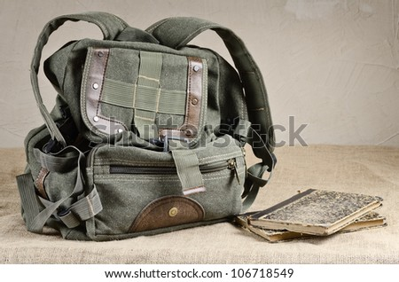 Tarpaulin backpack and old books on the canvas - stock photo