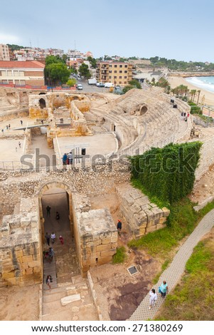 Tarragona, Spain - August 16, 2014: The Historical amphitheater of Tarragona with walking tourists, Catalonia, Spain, vertical photo - stock photo