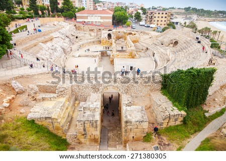 Tarragona, Spain - August 16, 2014: The Historical amphitheater of Tarragona with walking tourists, Catalonia, Spain - stock photo