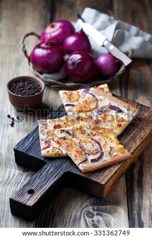 Tart flambee with purple onions, bacon and apples (Flammkuchen), selective focus - stock photo