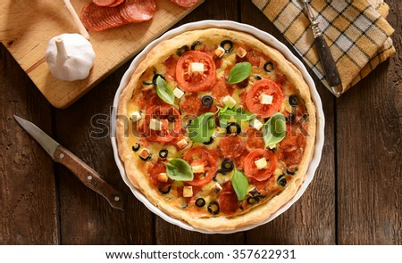 Tart (Quiche) with tomatoes, basil, salami, black olives and cheese - stock photo