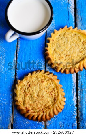 Tart with filling open on a wooden surface - stock photo