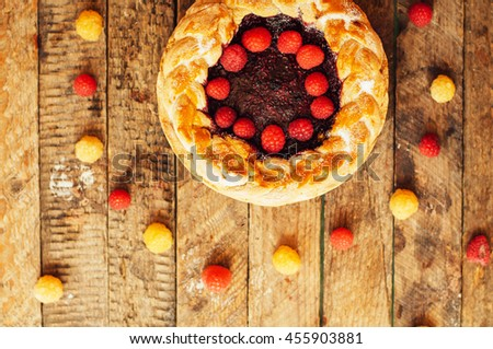 Tart with fresh berries.  Homemade  tart decorated with berries. Food: Cranberry and Raspberry upside down cake. a very natural and easy cake with olive oil and topped with caramelized raspberries - stock photo