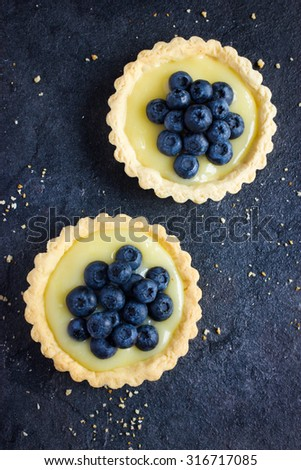 Tart with lemon curd and fresh blueberry, top view - stock photo