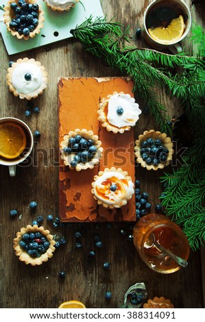 Tart with lemon curd and fresh blueberry, top view. Dessert tartlets with blueberries on  wooden background. Mini lime curd tartlets with meringue. Holiday concept. Top view. - stock photo