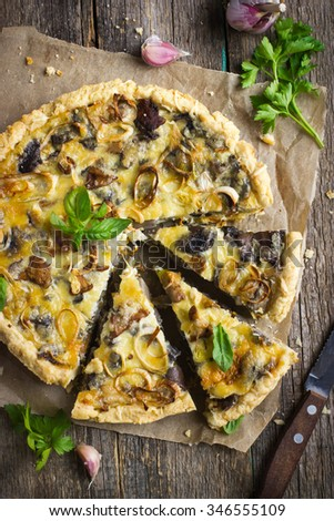 tart with mushrooms, leek and cheese on rustic background - stock photo