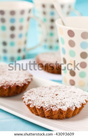 Tart with sugar and cups on blue background - stock photo