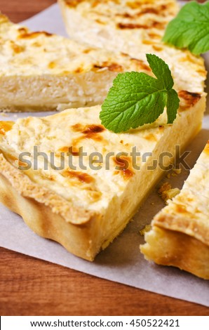 Tart with vegetables and cheese on wooden background. Selective focus.