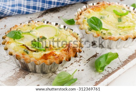 Tart with zucchini and cheese on a white wooden background. Selective focus - stock photo