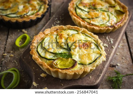 tart with zucchini, leek and cheese on rustic background - stock photo