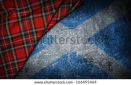 tartan textile on stone background with scotland flag - stock photo