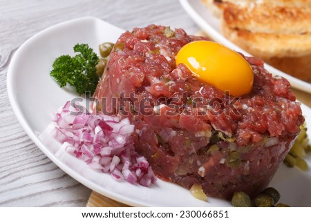 tartare meat with egg, onion and capers closeup on a white plate. horizontal  - stock photo