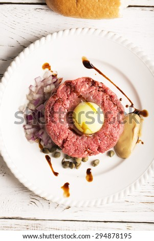 tartare with egg yolk, onions and capers closeup on a white plate - stock photo