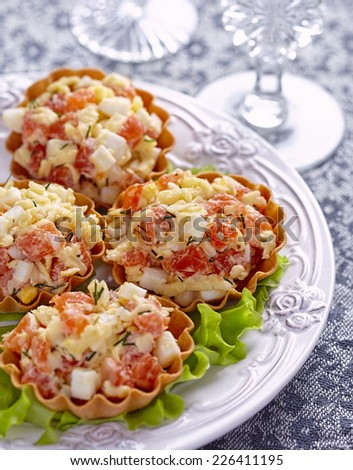 Tartlet stuffed with salmon salad with cheese and egg - stock photo