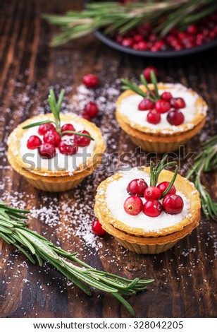 Tartlets of pastry with cream and fresh berries ripe cranberries and rosemary leaves sprinkled with coconut on the texture wooden background. selective Focus - stock photo