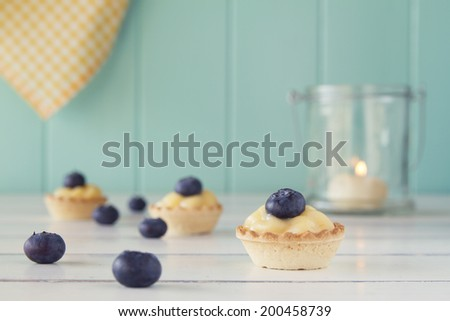 Tartlets with blueberries and pastry cream on a white wooden table with a robin egg blue background, a candle and a yellow checkered napkin. Vintage Style. - stock photo