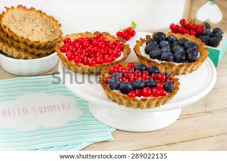 Tartlets with blueberries and red currant on a white cake stand. Empty pie shells and fresh fruits in the background. Colorful decoration. - stock photo