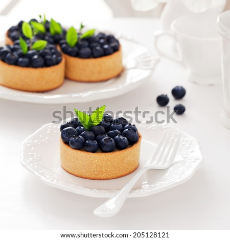 Tartlets with cream and blueberries, selective focus - stock photo