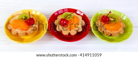Tartlets with fruits  on a white wooden table