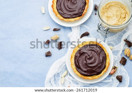 tartlets with peanut butter mousse and chocolate on a blue background. tinting. selective focus - stock photo