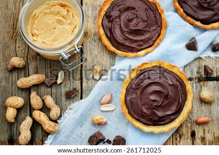 tartlets with peanut butter mousse and chocolate on a dark wood background. tinting. selective focus - stock photo