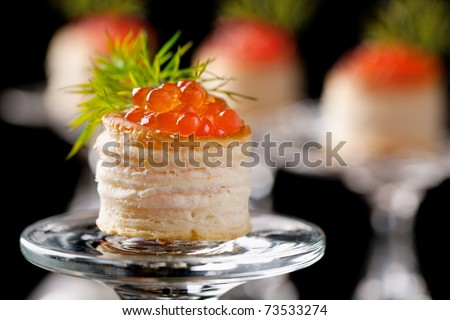 Tartlets with red caviar on black background - stock photo