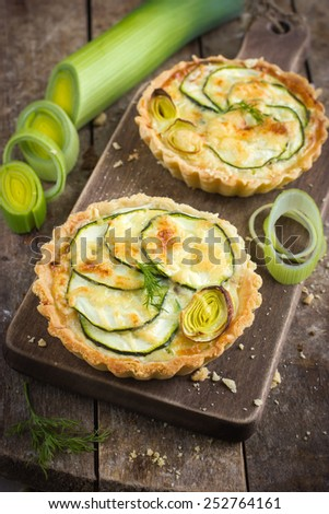 tartlets  with zucchini, leek and cheese on rustic background - stock photo